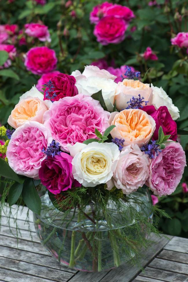 Обыкновенная стеклянная ваза с красивым букетом домашних роз