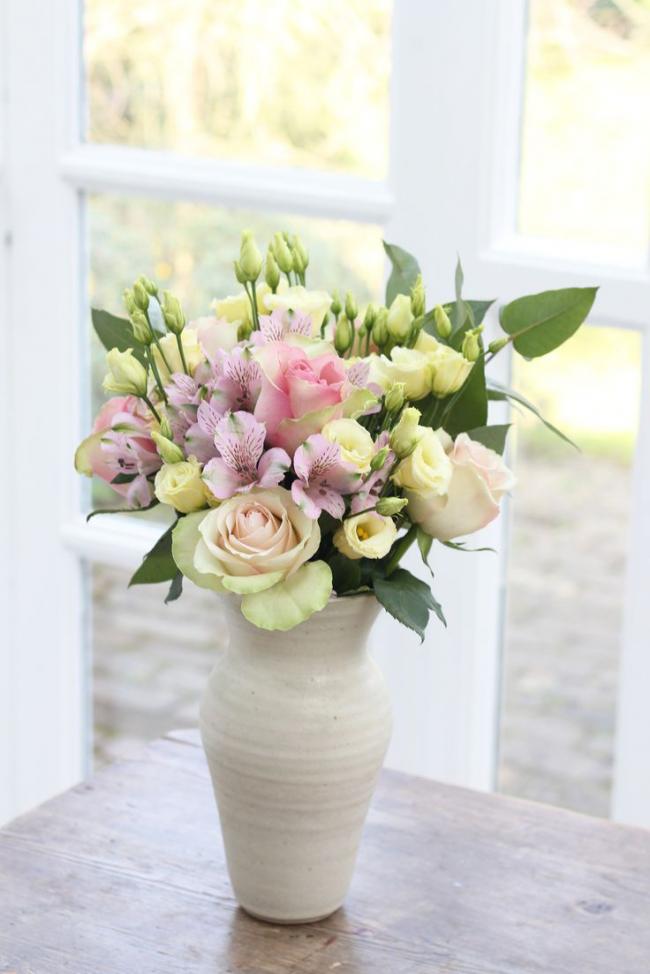 Розы в глиняной вазе в светлом уголке помещения