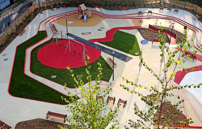 Детская площадка с зонами для игр. Место для песочницы выделено отдельно - внутри покрытия из резиновой крошки размещена песочница в виде островка с мостиком