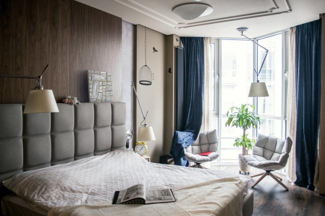 Современная небольшая спальня с ламинатом у изголовья кровати