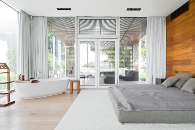 Просторная светлая спальня с большими окнами и деревянной отделкой стены у изголовья кровати