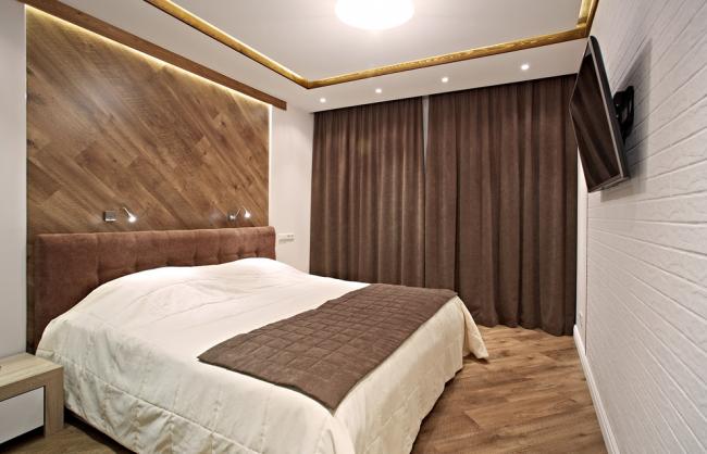 Диагонально расположенный ламинат коричневого цвета как украшение изголовья кровати