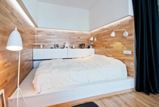 Современная спальня в скандинавском стиле с кроватью на подиуме и стенами отделанными ламинатом