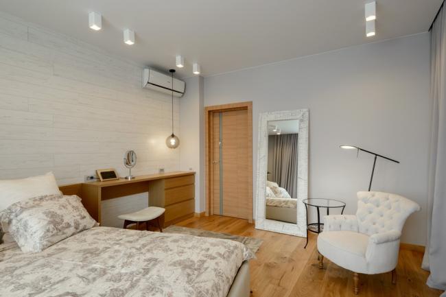 Белый ламинат на одной из стен хорошо смотрится со светло-коричневым ламинатом на полуспальни
