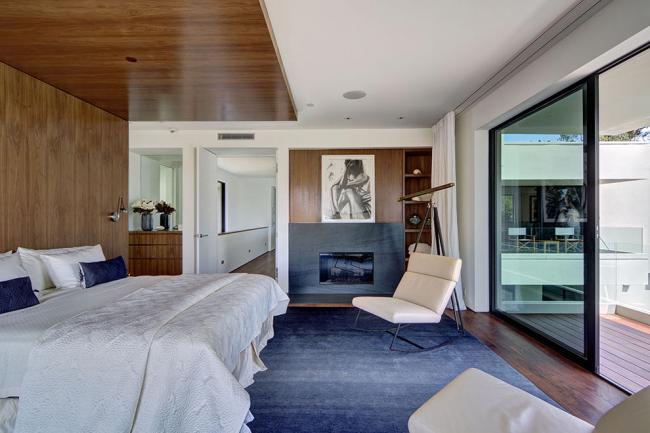 Ламинат на стене у изголовья кровати частично переходит на потолок
