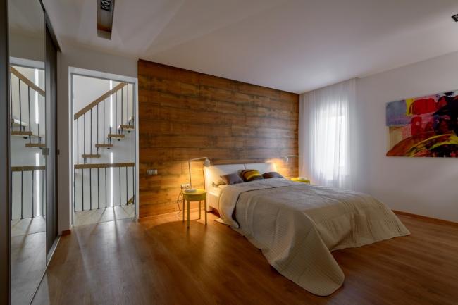 Коричневый ламинат на стене достаточно контрастирует на фоне белых стен и потолка