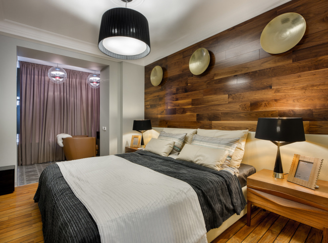 Красивый глянцевый ламинат на стене спальни хорошо смотрится в современном интерьер