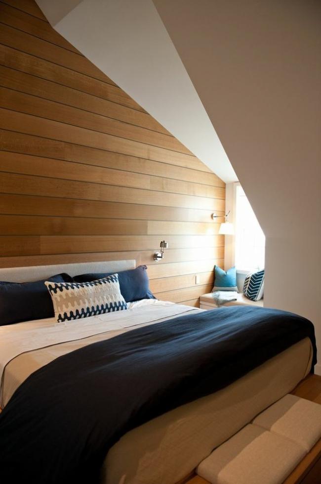 Маленькую мансардную спальню украшает ламинат, корым отделана одна из стен