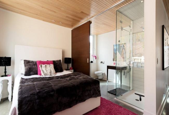 Современный интерьер спальни со стеклянной перегородкой в ванузел