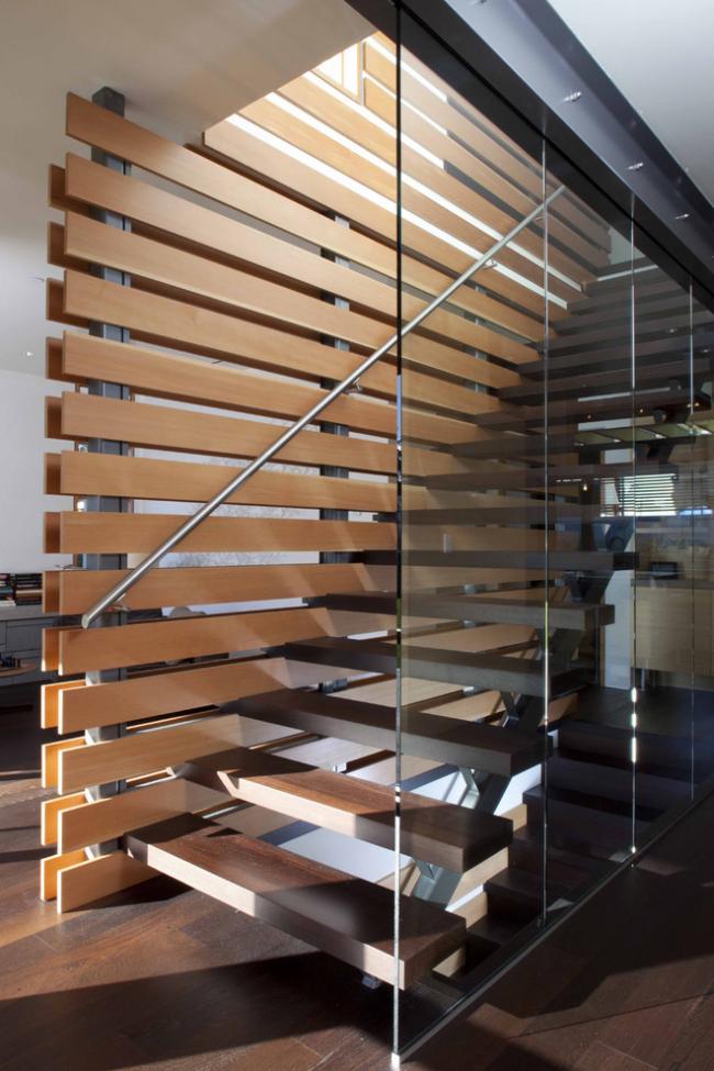 Современная лестница частного дома с перилами из нержавейки по одну сторону