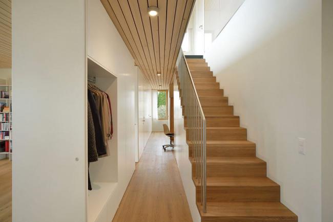 Светлый современный интерьер с деревянной лестницей и перилами из нержавеющей стали