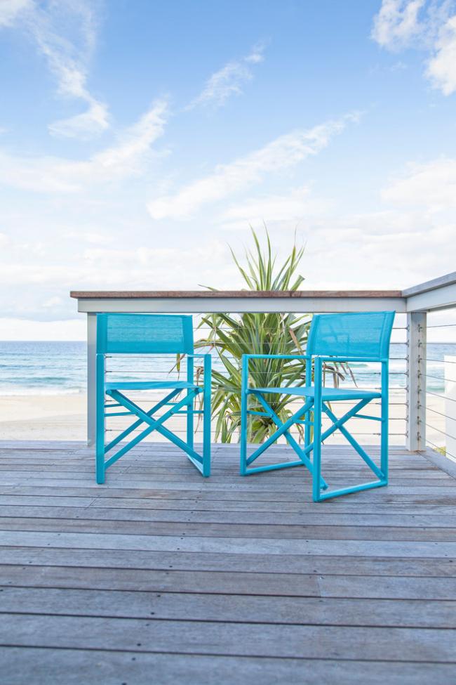 Небольшая терраса с голубыми складными стульями и прекрасным видом на море