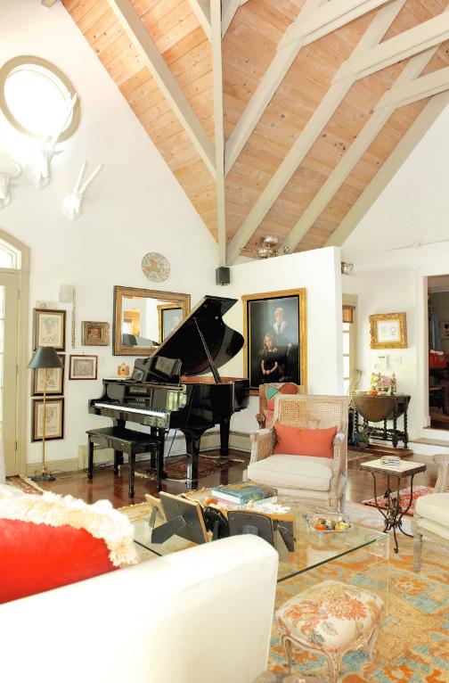 Гостиная с несколькими арт-объектами: оленьи рога, картины и зеркало в оригинальных рамах, кованый журнальный столик