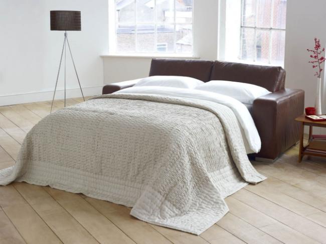 Контрастный кожаный диван в светлой просторной спальне