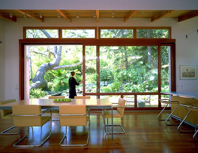 Огромные двери-купе из натурального дерева и стекла в частном загородном доме и вравду создают ощущение настоящего необъятного простора