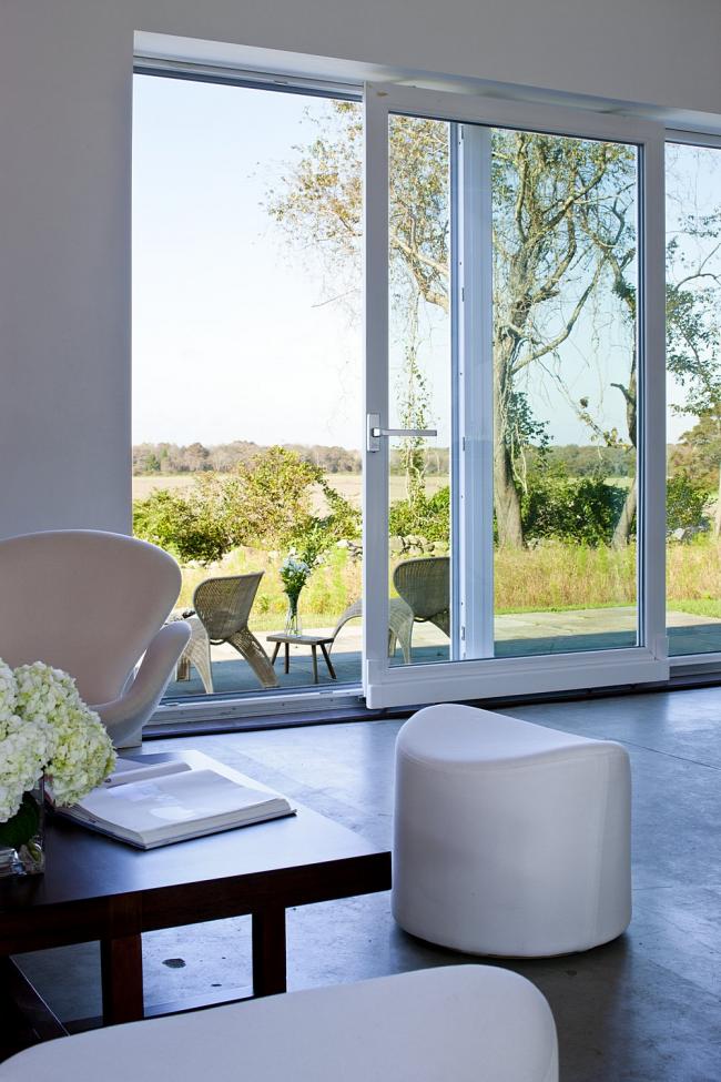 Большие стеклянные двери-купе - отличное решение для оформления выхода на задний дворик частного дома