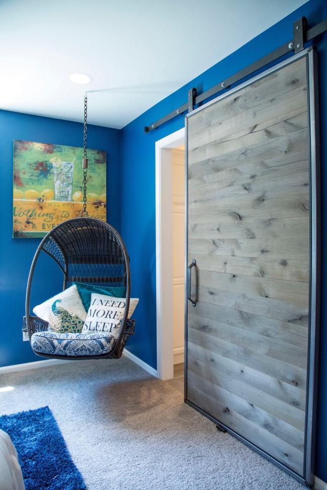 Дверь-купе с полотном из сероватого дерева отлично гармонирует с ярким синим цветом стен комнаты