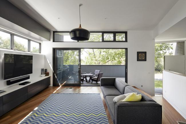 Просторная гостиная частного дома со стеклянной дверью-купе, что ведет в уютную зону отдыха во внутреннем дворике