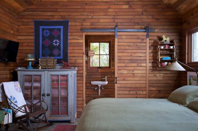 Очень атмосферная спальня загородного домика с деревянной дверью-купе