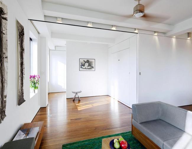 Просторная комната студийного плана с практически незаметной белоснежной дверью-купе