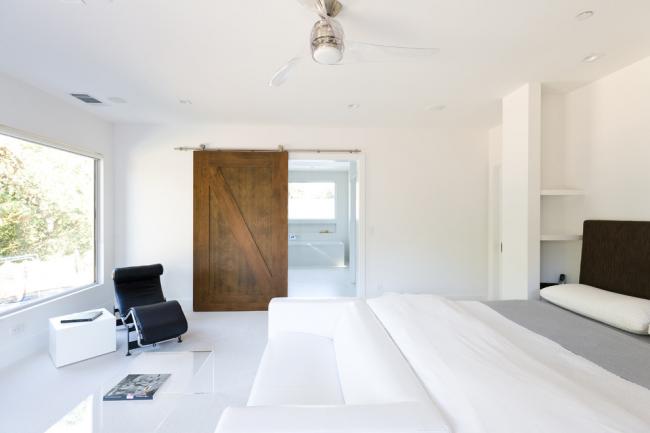 Очень яркий акцент на межкомнатной двери-купе из натурального дерева в белоснежной спальне