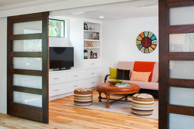 Комбинированные межкомнатные двери-купе из натурального дерева и матового стекла отлично дополняют гостиную в скандинавском стиле