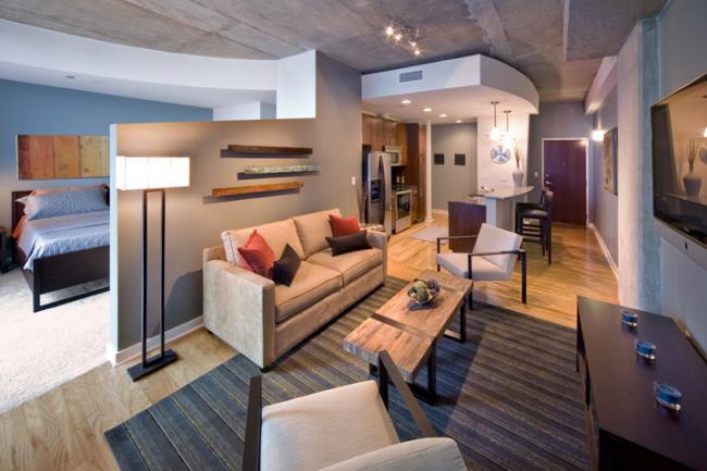 Красивое сочетание подвесных потолков и голых бетонных плит в интерьере квартиры-студии