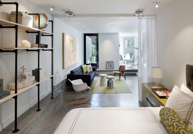 Легкая занавеса без рисунка на карнизе под потолком будет уместна для зонирования современной квартиры-студии