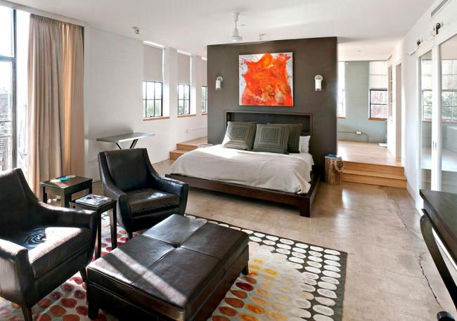 Стена, выкрашенная в темный цвет, поможет визуально отделить спальную зону от общего пространства