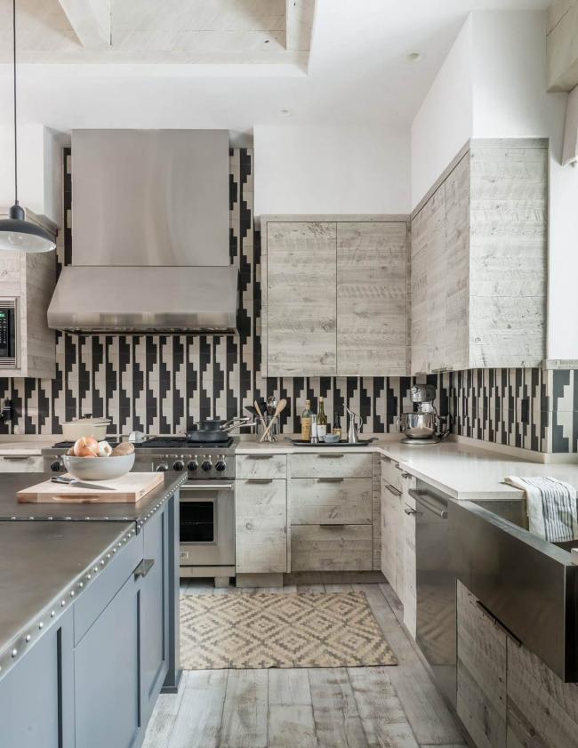 Необычный графический узор кухонного фартука отлично гармонирует с гарнитуром из светлого натурального дерева