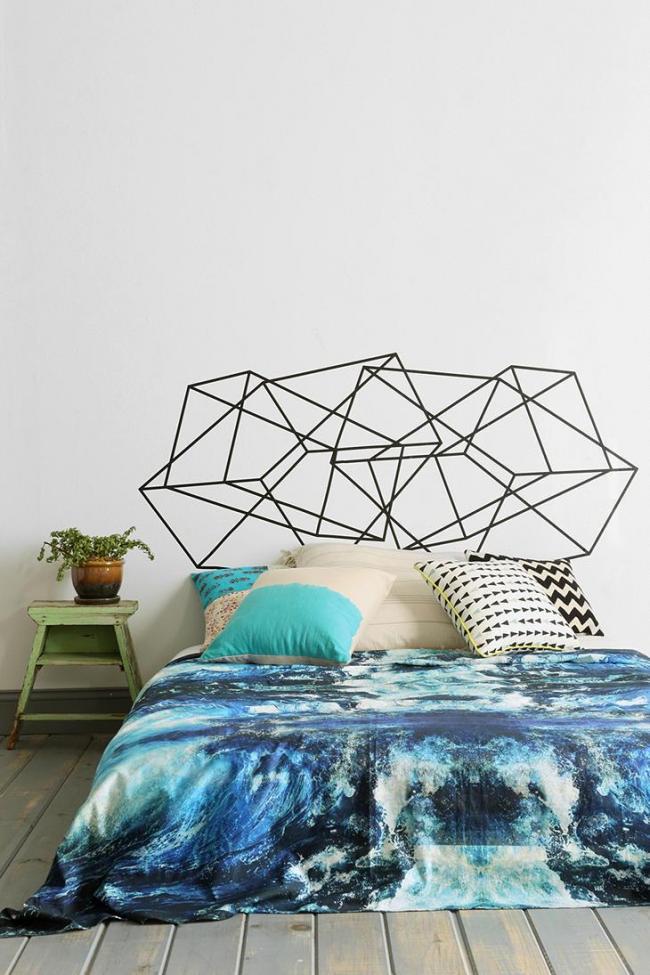 Просторная светлая спальня с необычным геометрическим рисунком над изголовьем кровати и ярким акцентом на постельном белье с морскими мотивами