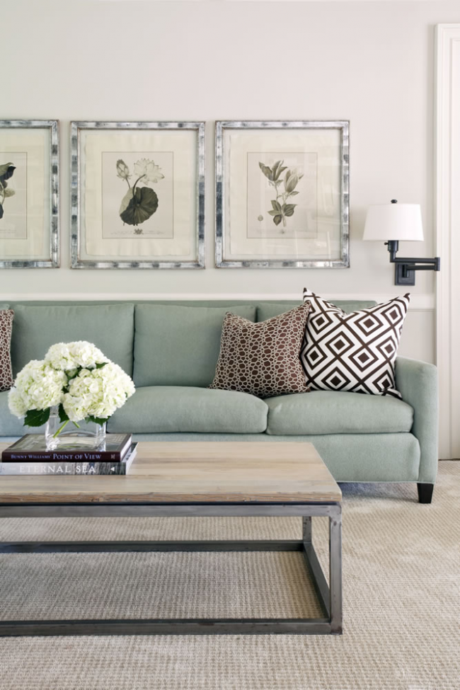 Небольшая гостиная в пастельных тонах с элементами графики на обшивках подушек и нежными рисунками в рамках