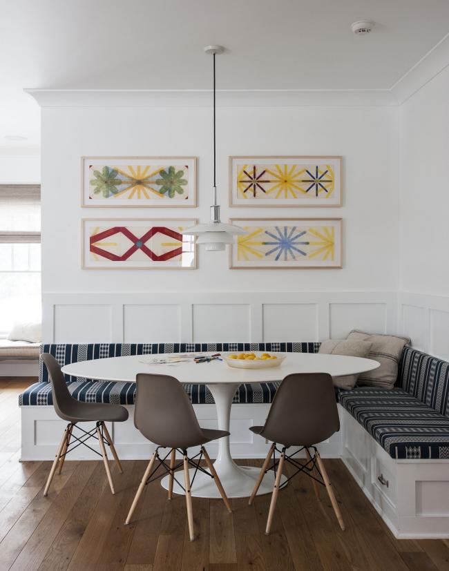 Обеденная зона кухни-студии в светлых тонах с графическими орнаментами на чехлах угловой тахты