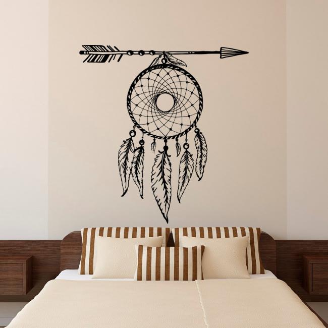 Ловец снов над изголовьем кровати в спальне в нежных кремовых тонах