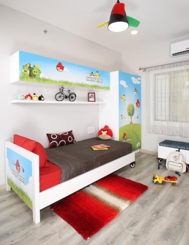Черная люстра с яркими деталями красного, желтого и зеленого цвета в интерьере детской комнаты