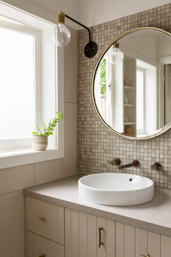 Красивое сочетание бежевой мозаики и белоснежной круглой раковины в дизайне ванной комнаты