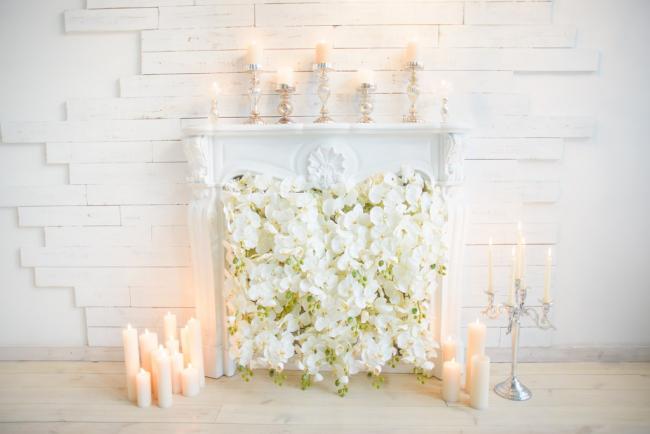 Белый резной каминный проем, украшенный цветами и свечами