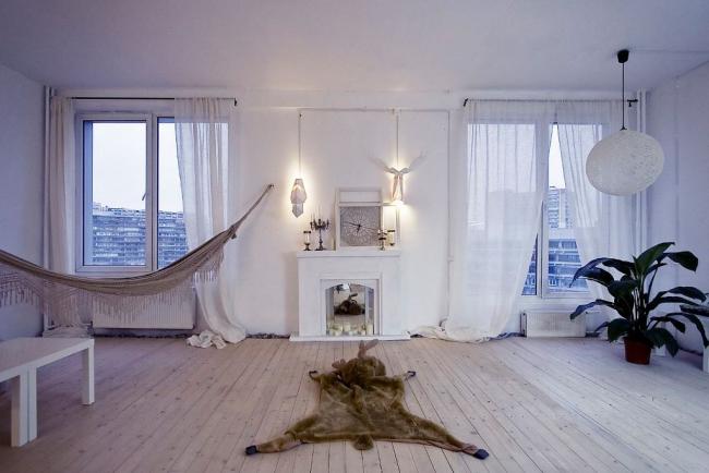 Белоснежная комната с зеркальным декоративным камином, отражающим свечи