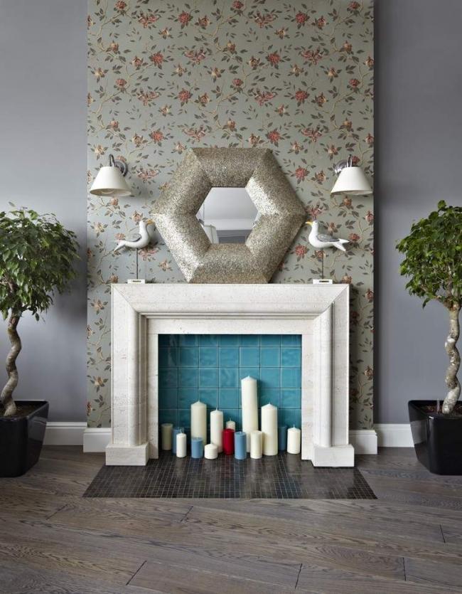 Условный вид декоративного камина с большим количеством разноцветных свечей