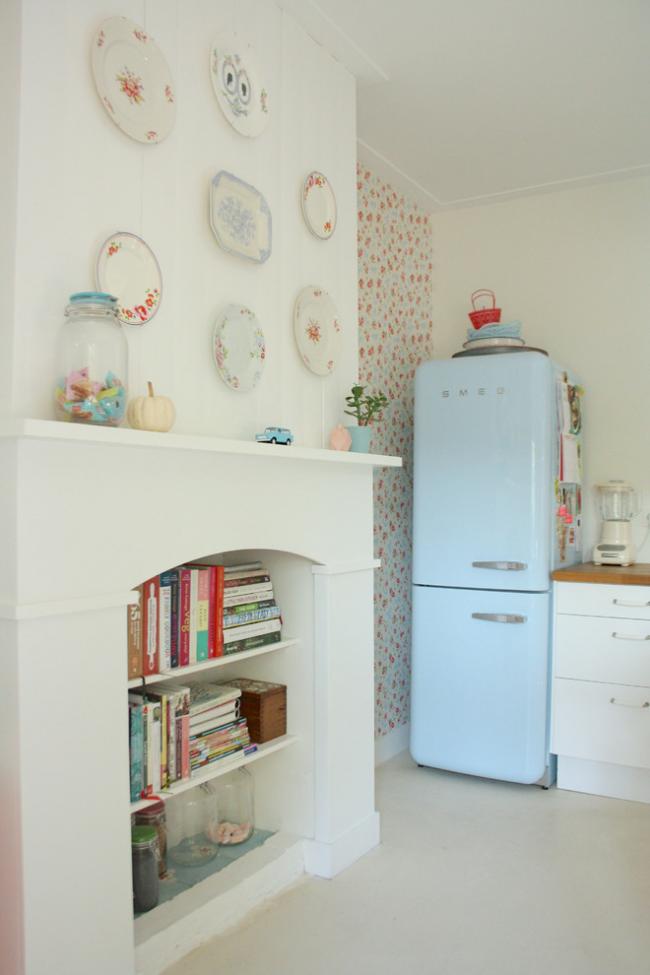 Декоративный камин в кухне можно использовать как стеллаж, хранить в нем книги с рецептами, разные баночки с сыпучими продуктами и другие мелочи