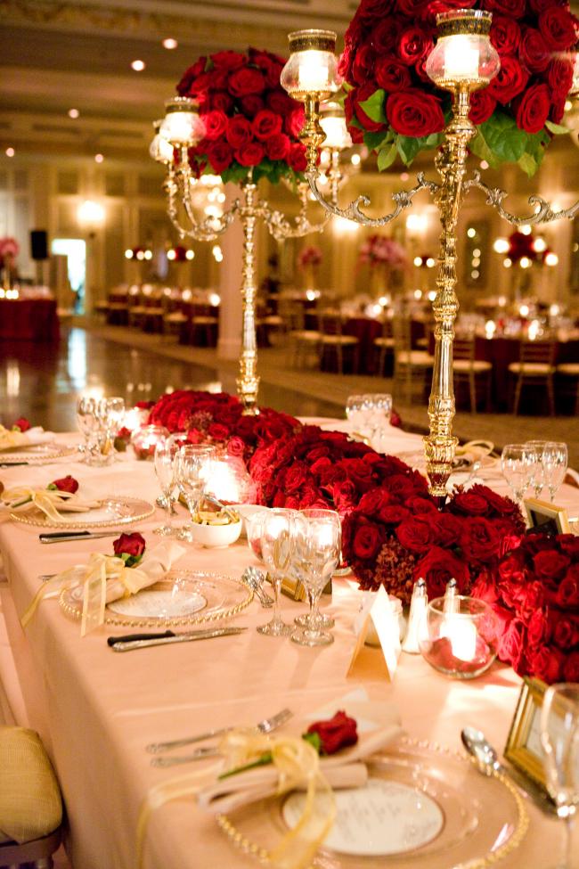 Красный цвет хорошо подходит для оформления центральных композиций на столах свадебного зала в зимней тематике