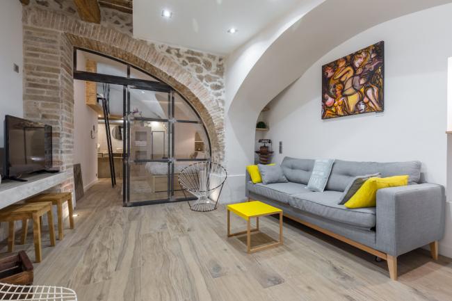Интересное сочетание гипсокартонной конструкции и грубого камня в отделке интерьера гостиной