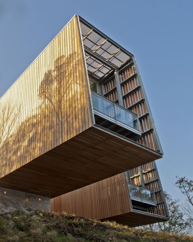 Дом из контейнеров с обшивкой деревом и крышей из поликарбоната