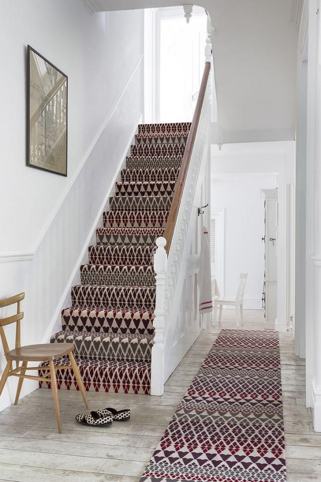 Ковровые дорожки с одинаковым принтом удачно декорируют лестницу и белоснежный коридор