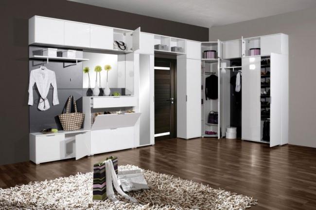 Угловая прихожая с многочисленными шкафчиками в контрастном белом цвете