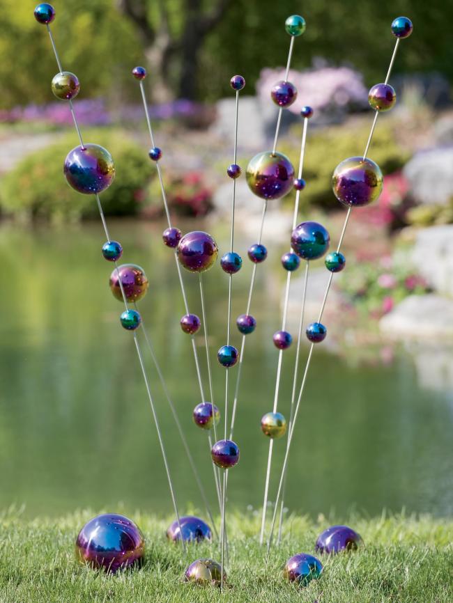 Переливающиеся небольшие шары, нанизанные на металлические прутья придадут космический эффект вашему саду
