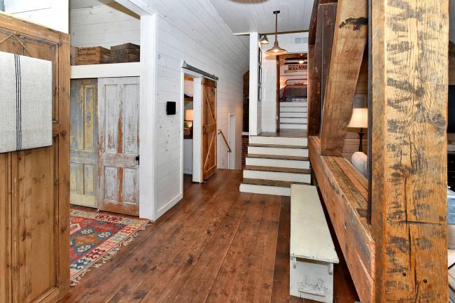 Прихожая в стиле лофт в загородном доме имеет множество деревянных элементов - окрашенного, натурального, искусственно состаренного