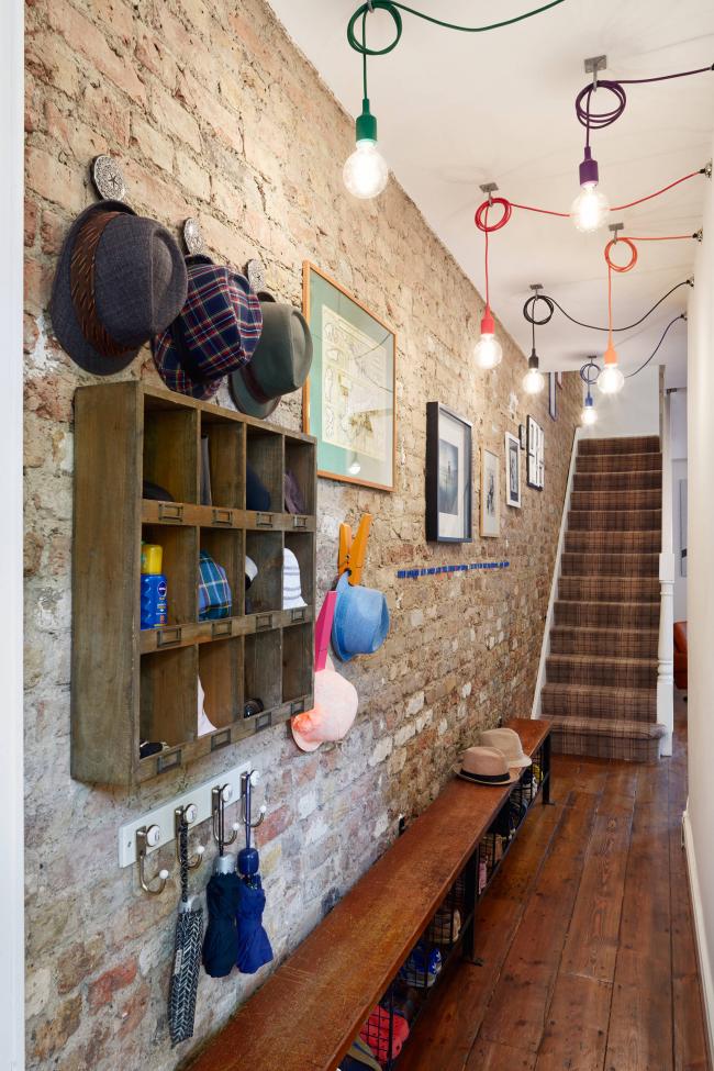 Прихожая в частном доме в стиле лофт. Каминная кладка, стильные лампы, открытые полки и длинная лавочка с возможностью хранить вещи