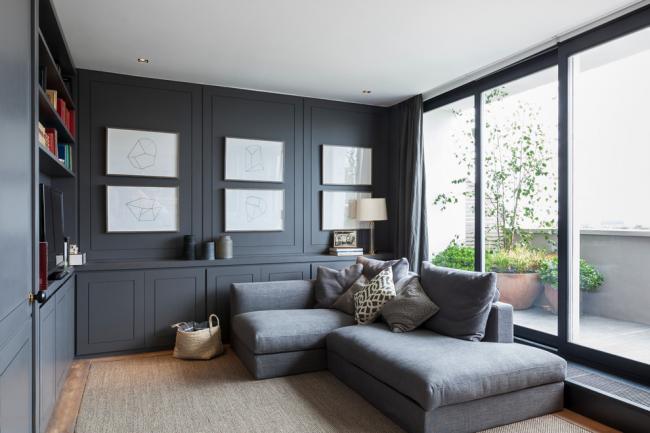 Расположение дивана спинкой к окну пользуется популярностью у тех, кто любит читать. Низкая спинка не загромождает пространство