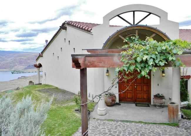 Крыльцо загородного имения, обвитое лозами молодого винограда